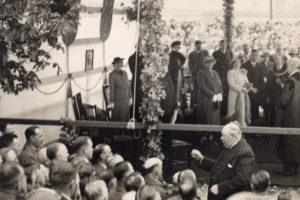 Luther conducting the Orpheus for a royal visit in 1938 in a marquee at Hyde Park Corner, Colne. Queen Elizabeth the Queen Mother and King George VI can be seen directly behind him